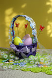 Easter eggs basket. Painted eggs. Easter background. Easter theme decoration. Colorful easter eggs on yellow background Royalty Free Stock Image