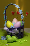 Easter eggs basket. Painted eggs. Easter background. Easter theme decoration. Colorful easter eggs on yellow background Stock Photo