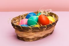 Easter eggs in basket on pink stock photography