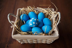 Easter eggs in a basket on rustic wooden background, selective focus image, Happy Easter. Blue Easter eggs Royalty Free Stock Images