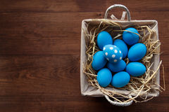 Easter eggs in a basket on rustic wooden background, selective focus image, Happy Easter. Blue Easter eggs Royalty Free Stock Photos