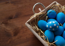 Easter eggs in a basket on rustic wooden background, selective focus image, Happy Easter. Blue Easter eggs Royalty Free Stock Photo