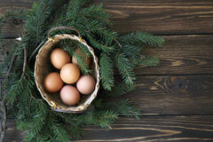 Easter eggs in the basket on rustic wooden. Easter natural colour eggs in the nest on rustic wooden background Royalty Free Stock Image