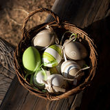 Easter eggs in the basket on rustic wooden surface Royalty Free Stock Image