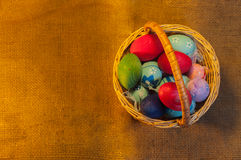 Easter Eggs in Basket on sackcloth background Royalty Free Stock Photos