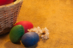 Easter Eggs and a Basket on sackcloth background Royalty Free Stock Images