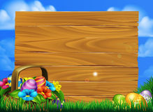Easter Eggs Basket Sign. Cartoon easter eggs basket sign scene with a basket of chocolate Easter eggs in a field with a big wooden sign Royalty Free Stock Image