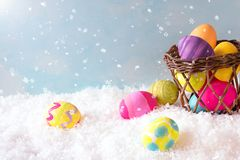 Easter Eggs and Basket in the Snow Scene outside with sky background with room or space for copy, text or your words. Horizontal