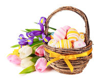 Easter eggs in a basket and spring flowers Stock Images