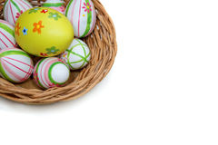 Easter eggs in a basket from top corner. On white background Royalty Free Stock Image