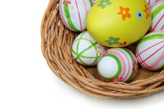 Easter eggs in a basket from top right. Easter eggs in a basket on white background from top view Stock Photos