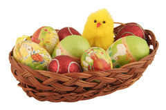 Easter eggs in a basket with toy chick. Isolated on white Stock Photos
