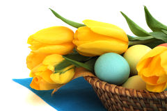 Easter eggs in basket with tulips Stock Photos