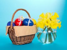 Easter eggs in basket and vase with narcissuse Stock Photography