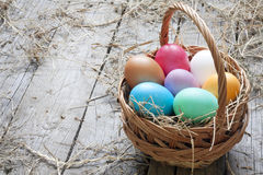 Easter eggs in basket on vintage wooden planks Royalty Free Stock Photography