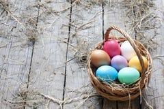 Easter eggs in basket on vintage wooden planks Stock Images