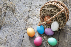 Easter eggs in basket on vintage wooden planks Royalty Free Stock Photos
