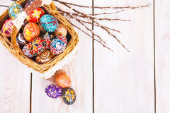 Easter eggs in a basket on white plank background. Stock Photography