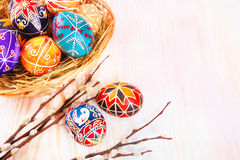 Easter eggs in a basket on white plank background. Stock Photo