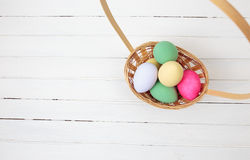 Easter eggs in basket on white wood Stock Photos