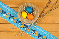 Easter eggs in basket and willow twigs Stock Photo