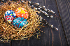 Easter eggs in a basket with willow twigs on a wooden table. Stock Photos
