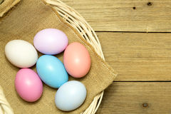 Easter eggs in the basket on wood background. Easter eggs in the basket on brown wood background Royalty Free Stock Photo