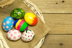 Easter eggs in the basket on wood background. Easter eggs in the basket on brown wood background Royalty Free Stock Images