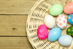 Easter eggs in the basket on wood background. Easter eggs in the basket on brown wood background Stock Images