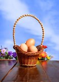 Easter eggs in a basket on wood texture on blue sky background. Royalty Free Stock Photo
