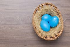 Easter eggs in the basket on wooden background. Easter eggs in the basket and nest on wooden background royalty free stock photography