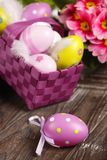 Easter eggs in basket. On wooden background Stock Photos