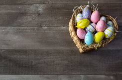 Easter eggs in a basket. On a wooden background stock photo
