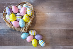 Easter eggs in a basket. On a wooden background royalty free stock image