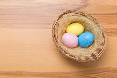 Easter eggs in the basket on wooden background stock image