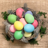 Easter eggs in basket on wooden background Stock Images