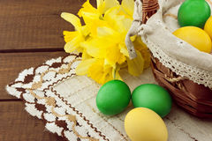 Easter eggs in the basket on wooden table with bouquet of daffodil Stock Images