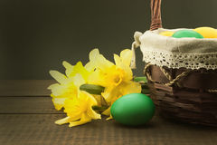 Easter eggs in the basket on wooden table with bouquet of daffodil Stock Photo