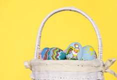 Easter eggs in basket on yellow background Stock Images