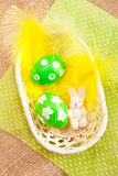 Easter eggs in a basket  with yellow feathers Royalty Free Stock Photos