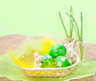 Easter eggs in a basket  with yellow feathers Royalty Free Stock Images