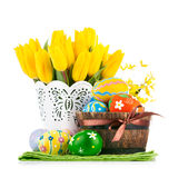 Easter eggs in basket with yellow tulips Royalty Free Stock Image