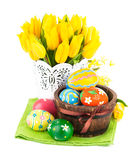 Easter eggs in basket with yellow tulips Royalty Free Stock Photos