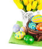 Easter eggs in basket with yellow tulips Royalty Free Stock Photo