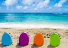 Easter eggs on the beach. Four color Easter eggs on the sandy beach by the ocean Royalty Free Stock Photography