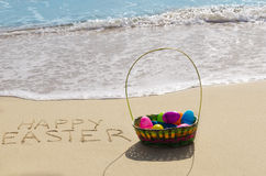 Easter eggs on the beach. Four color Easter eggs on the sandy beach by the ocean Stock Photos