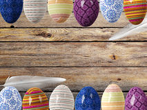 Easter eggs and bird feathers on wood background with space Stock Images