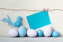 Easter eggs and bird in pastel colors with a blank card on a white wooden background Royalty Free Stock Photo