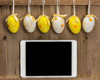 Easter eggs and Blank empty tablet computer in a wooden background stock photography