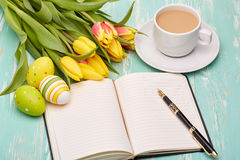 Easter eggs, blank daily log and tulips. Stock Photography